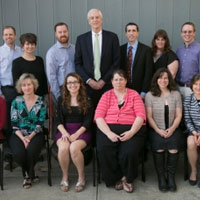 24 staff members graduate with higher ed degrees posed with interim president Hunter Rawlings