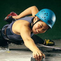 Smiling woman with helmet climbs up face of wall