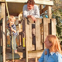 Young couple with child playing in playhouse