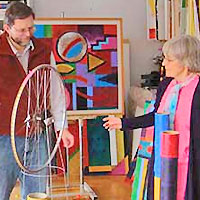 Woman artist shows her work to a visitor in her studio