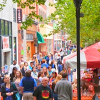 Pleasant summer day's view of Ithaca downtown, crowds of people in street