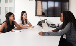 3 women sitting at conference table
