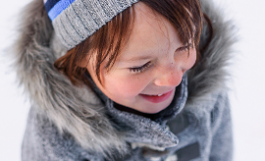child bundled up in winter coat & hat