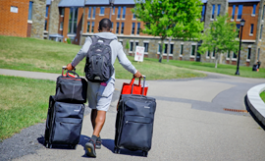 young man with suitcases headed toward dorm
