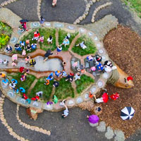 view from above of children playing on earthen turtle