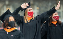 3 women in caps and gowns wearing face masks