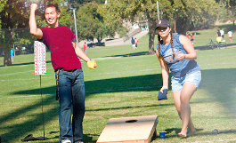 photo of man and woman playing cornhole