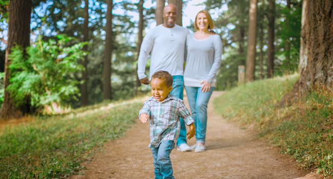 Mixed race couple and their young child on walk in forest