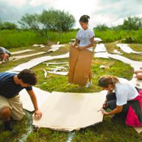 a group of students working together to build a labyrinth in a field