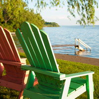 a pair of inviting Adirondack chairs lounge lakeside under a willow tree