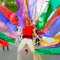 woman in parade artistically costumed as a giant colorful peacock.