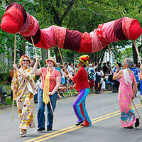 brightly costumed paraders carry red caterpillar aloft