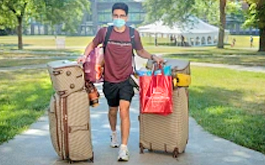 student with bags walking toward viewer