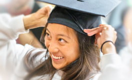 young woman smiles trying on mortarboard