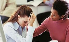 A woman comforts a colleague in an office setting