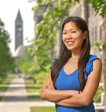 Confident, smiling young woman, McGraw tower in background