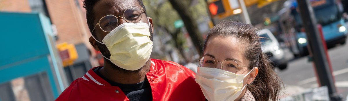 African-American man and Asian-American woman wearing face masks on street