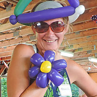 Smiling woman with balloon hat & flower