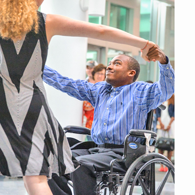 young man in wheelchair dances with woman