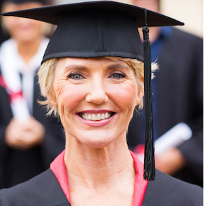 mature woman in gown & mortarboard smiling