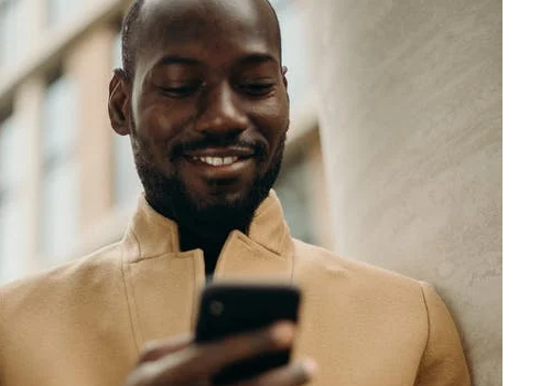 Black man smiling looking at phone