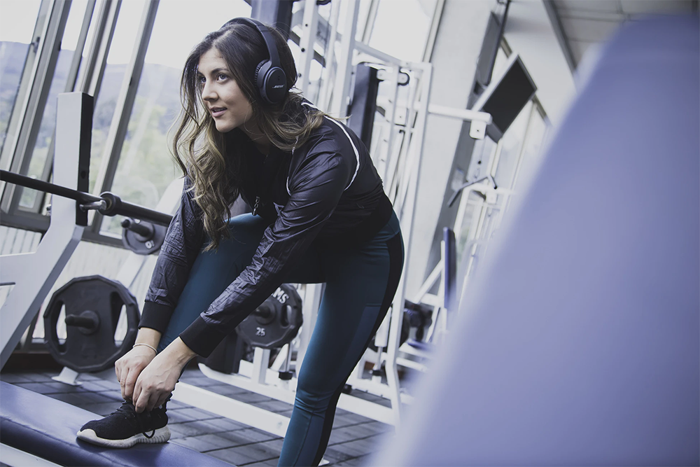 woman with headphones in gym tying shoe