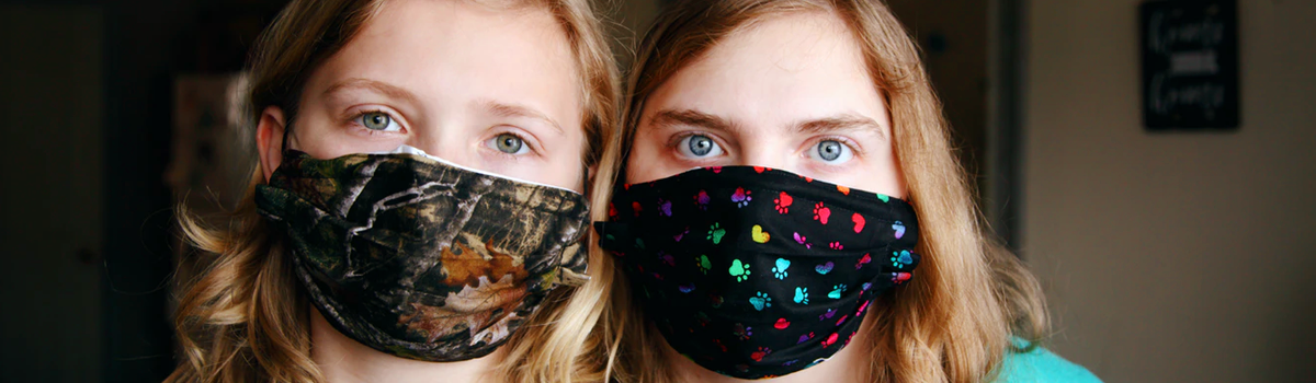 two girls wearing colorful face masks