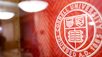 Cornell seal on red wall, angle, soft focus