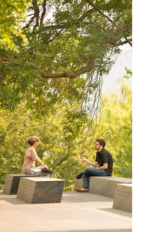two people chatting among trees at sesquicentennial monument