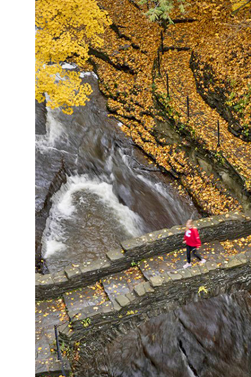 aerial view of woman crossing stone bridge over gorge in autumn
