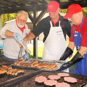 3 men grilling sausages & burgers at BBQ