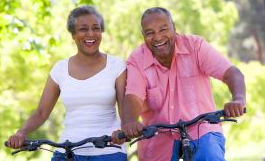 Black senior couple outdoors riding bikes laughing