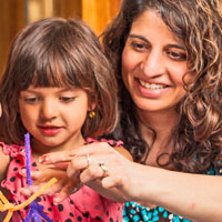 mother and daughter holding science project made of pipe cleaners