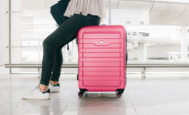 woman sitting on pink roller suitcase