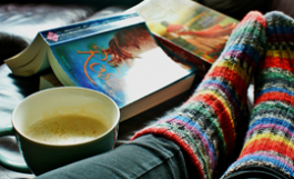 cozy cup of tea, book, and feet in colorful stripey socks