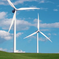 two modern windmills on a green hill against a blue sky