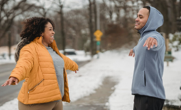 Black man and woman exercising outdoors on snowy sidewalk